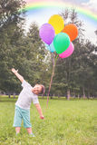 Happy child with balloons and beautiful rainbow outdoor Stock Photo