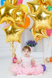 Happy child with balloons on his first birthday. Portrait of a little redheaded girl with dark grey eyes,a ridiculous smile,a pink bow on its head, in a Royalty Free Stock Images