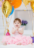 Happy child with balloons on his first birthday. Portrait of a little redheaded girl with dark grey eyes,a ridiculous smile,a pink bow on its head, in a Stock Image