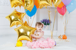 Happy child with balloons on his first birthday. Portrait of a little redheaded girl with dark grey eyes,a ridiculous smile,a pink bow on its head, in a Royalty Free Stock Photo
