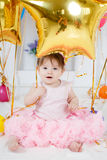 Happy child with balloons on his first birthday. Portrait of a little redheaded girl with dark grey eyes,a ridiculous smile,a pink bow on its head, in a Royalty Free Stock Photos