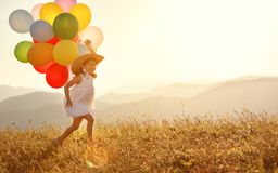 Happy child with balloons at sunset in summer Stock Image