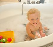 Happy child bathes in a bathroom Stock Photography