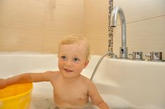 Happy child bathes in a bathroom Stock Images