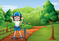 A happy child with a bike at the pathway with a wooden fence Stock Photo