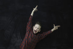 Happy child on blackboard background. Excited child with hands raised up against а blackboard background stock photo