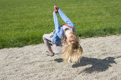 Happy Child blond girl (age 5) rids on Flying Fox play equipment in a children's playground. royalty free stock images