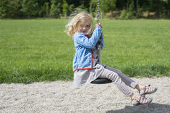 Happy Child blond girl (age 5) rids on Flying Fox play equipment in a children's playground. royalty free stock image