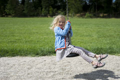Happy Child blond girl (age 5) rids on Flying Fox play equipment in a children's playground. stock photo