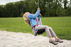 Happy Child blond girl (age 5) rids on Flying Fox play equipment in a children's playground. stock image