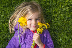Happy child blond girl lying on grass. Funny kid playing in park. Beautiful spring flowers. Royalty Free Stock Photo