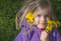 Happy child blond girl lying on grass. Funny kid playing in park. Beautiful spring flowers. Stock Photography