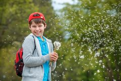 Happy child blowing dandelion flower outdoors. Boy having fun in spring park. Blurred green background royalty free stock photo