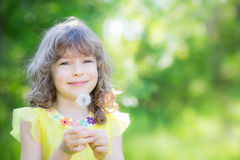 Happy child blowing dandelion flower outdoors Royalty Free Stock Photography