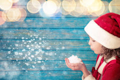 Happy child blowing a handful of snow Royalty Free Stock Image