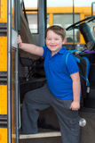 Happy child boarding school bus Stock Image