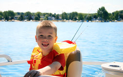 Happy Child on Boat. A happy, smiling, young boy wearing a life vest as he sits out on a lake on a pontoon boat. There are fishing poles behind him stock image