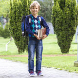 Happy child with books and a backpack go to school. Outdoor. Royalty Free Stock Photos