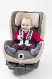 Happy child in booster seat for a car in light background. Laughing child in booster seat for a car in light background Stock Photos