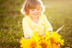 Happy child with bouquet of beautiful sunflowers. Sunny day, summer vacation. Cute little girl with yellow sunflowers, outdoor portrait stock images