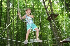 Happy child boy in adventure park in safety equipment Royalty Free Stock Photos