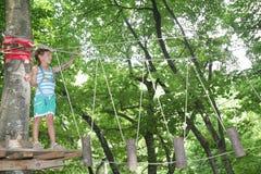 Happy child boy in adventure park in safety equipment Stock Photos