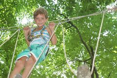 Happy child boy in adventure park in safety equipment Stock Photo
