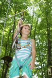 Happy child boy in adventure park in safety equipment Royalty Free Stock Image