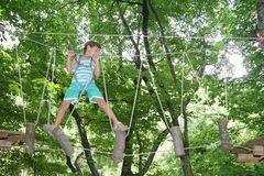 Happy child boy in adventure park in safety equipment. Young happy child boy in adventure park in safety equipment Royalty Free Stock Photos