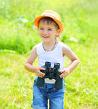 Happy child boy with binoculars outdoors in summer Royalty Free Stock Photos