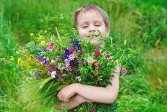 Happy child boy with bouquet of wild flowers. In his hands enjoying by Summer stock photo