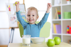 Happy child boy eating breakfast with hands up Stock Photo