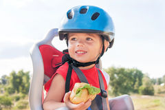 Happy child (boy) is eating lunch (snack) during bicycle ride. Stock Photos