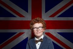 Happy child boy english studen looking up on the UK flag background. Learn English concept.  stock image