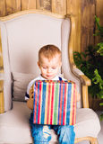 Happy child boy with gift box near Christmas tree. Royalty Free Stock Images