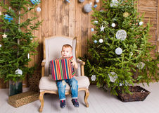 Happy child boy with gift box near Christmas tree. Happy boy with gift box near Christmas tree Stock Photo