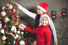 Happy child, boy and girl decorating a christmas tree Stock Images
