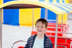 Happy child boy having fun in amusement park. Royalty Free Stock Image
