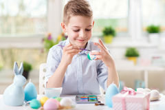 Happy child boy having fun during painting eggs for Easter in spring Stock Image