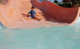 Happy child boy having fun in water park Stock Photos
