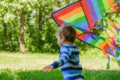 Happy child girl with a kite running on meadow in summer in nature stock photography