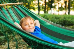 Happy child boy lying in a hammock in garden. Summer holidays concept. The child is resting in nature. Cute kid enjoy summer royalty free stock image
