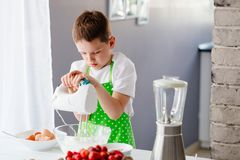 Happy child boy mixing dough in glass bowl Royalty Free Stock Image