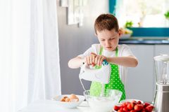 Happy child boy mixing dough in glass bowl Royalty Free Stock Photo