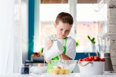 Happy child boy mixing dough in glass bowl Stock Photography