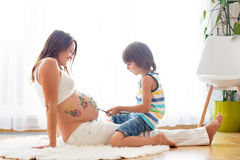 Happy child, boy, painting on mommy`s pregnant belly. With paint, isolated on white royalty free stock image