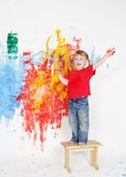 Happy child boy painting wall with colours Stock Images