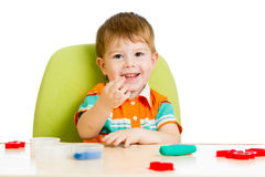 Happy child boy playing with colorful clay Royalty Free Stock Photos