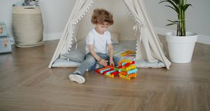 Happy child playing with construction set sitting in tent in apartment. Happy child boy is playing with construction set sitting in beautiful tent in apartment stock footage