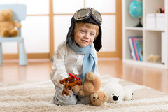 Happy child boy playing with wooden toy airplane and teddy bear in children room Stock Photo